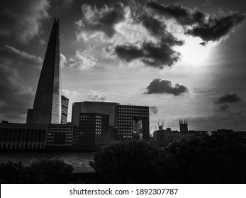 Black and white photo of The Shard in London in the distance with sun peeking between clouds
