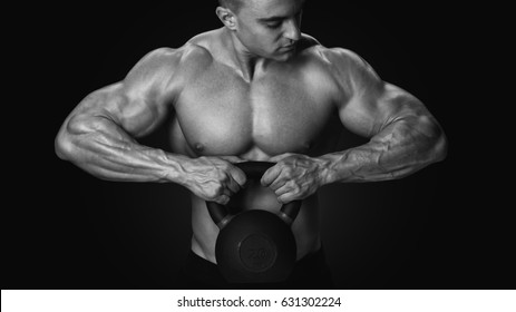 Black and white photo of shirtless young athlete with muscular body exercising crossfit with kettle bell on black background Intensive cross training
