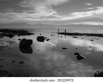 Black and white photo showing two figures in distance, on spit of land on rocky beach. Shoreline is cluttered with large rocks. Dramatic sky with clouds, mountains in distant background