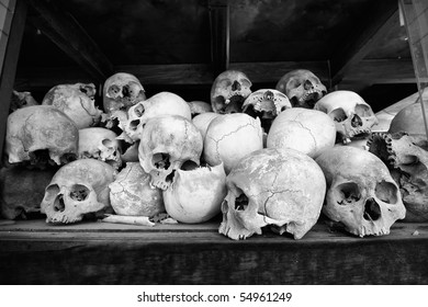 Black and white photo of the skulls of torture victims resting in a stupa at the Killing Fields outside of Phnom Penh, Cambodia.