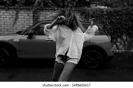 Black and white photo of slim girl in oversize white shirt and jeans shorts. Dancing outdoor next to the car. Long hair shaking, raised hands. Summer raining weather. Freedom and crazy