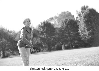 Black and white photo of Smiling and healthy senior woman throwing disc in park