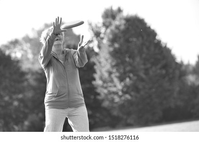 Black and white photo of Smiling and healthy senior woman catching disc in park