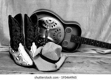 black and white photo of snakeskin cowboy boots with a cowboy hat and a vintage dobro resonator guitar. The country western themed items are on a rustic wooden surface. The snakeskin is python.