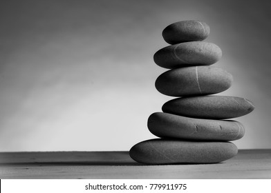 black and white photo of stack of six stones