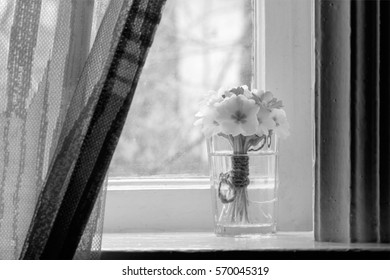 black and white photo, still life a bouquet of primroses on the windowsill in a village house