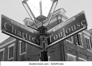 A black and white photo of the street name signs at the Chartres and Toulouse streets intersection in the French Quarter of New Orleans.
