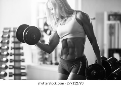 Black and white photo. Strong woman bodybuilder with white hair pumps up the muscles lifting dumbbells in the gym. Sports and fitness. Fitness woman in the gym. Fitness woman with dumbbell.