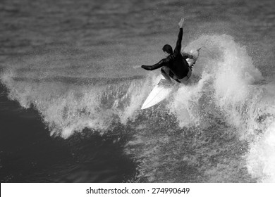 A black and white photo of a surfer carving a radical off-the-lip.