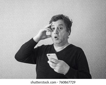 Black and white photo of surprised middle aged caucasian man with smartphone