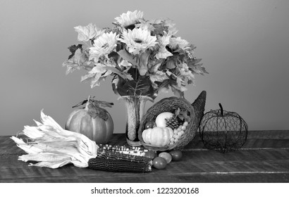 Black and White photo of a table arrangement:  Vase with Fake Flowers, a stuffed cornucopia, Indian Corn with husk on Claimed wood table