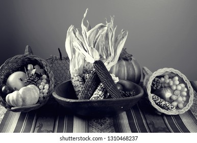 Black and White photo of a table arrangement:  two stuffed cornucopia, Indian Corn with husk in old wood bowl