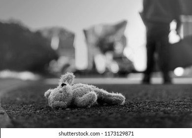 Black and white photo of Teddy bear laying  on the street with blurry background of school kid carrying school bag,Toy bear was left lying on the street,missing children or kidnap school kids concept