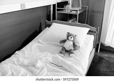 Black and white photo of teddy bear on hospital bed