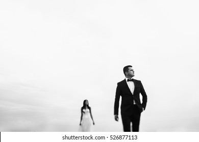 Black and white photo of thoughtful groom looking far away while pretty bride stands behind him