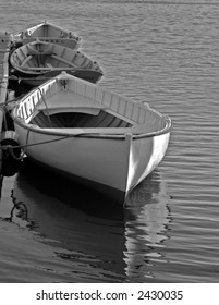 Black and white photo of three boats moored on the Mystic River in Connecticut
