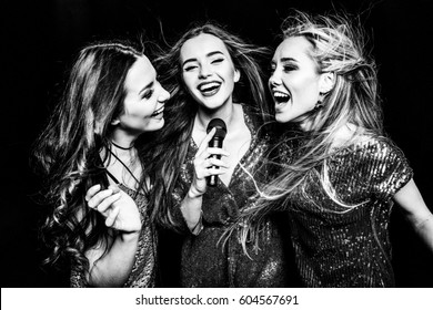 Black and white photo of three gorgeous women in festive dresses singing karaoke isolated on black
