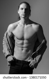 Black and white photo of a topless man. Gray background. Studio photo session