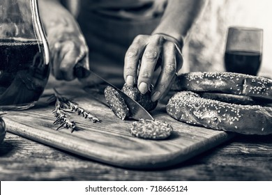 black and white photo. Traditional Italian red wine, salami, rosemary, bread. Close up of a person's hand cut salami on a kitchen board. movie effect