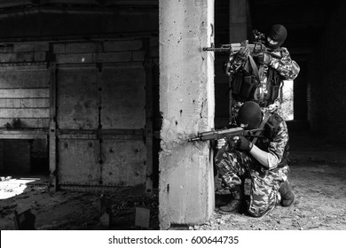 Black & white photo of two terrorists attack with assault rifles.Dangerous military men in black balaclava masks shoot with guns in ruined buildings