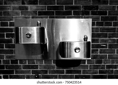 A black and white photo of two water fountains in the playground