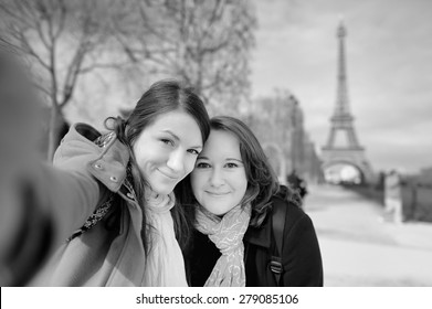 Black and white photo of two young woman taking a self portrait (selfie) near the Eiffel tower