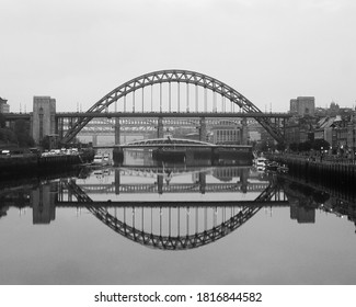 Black and white photo of the Tyne bridge on a misty foggy morning on the river Tyne, Newcastle upon Tyne, the river is so calm that there is a perfect reflection of the bridge in the water