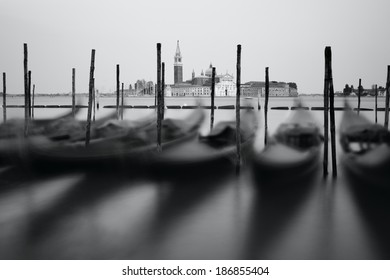 Black and white photo of Venice seafront with gondolas on the waves. Venice, Italy
