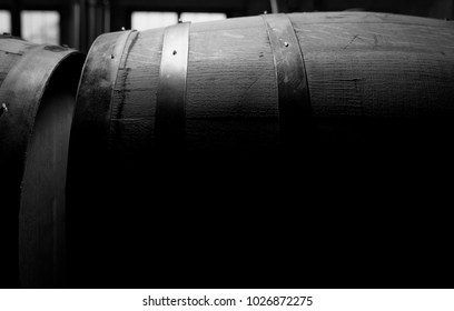A black and white photo of a vintage whiskey barrel aging in a distillery.