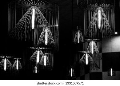 Black and white photo of wire chandeliers hanged from ceiling. Modern lampshades. Lamp with long light bulb inside. Abstract background. Geometric line shapes. Futuristic backdrop. Interior decoration