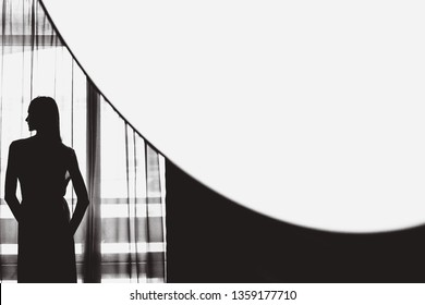 black and white photo of woman silhouette near the window. secret concept. woman shadow. woman looking into the windows