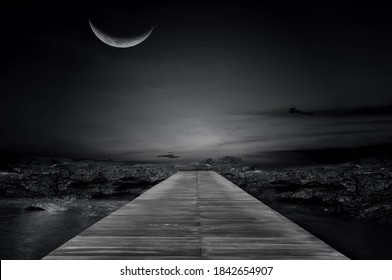 Black and white photo of the wooden bridge in the dark morning, the half moon night beautifully.