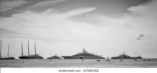 Black and white photo of yachts worth billions of dollars aligned in french riviera
