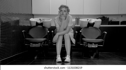 Black and white photo of young girl sit in armchair with washbasin in salon