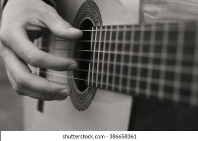 black and white photo. The young man playing an acoustic guitar. guitarist playing on a wooden guitar, music art