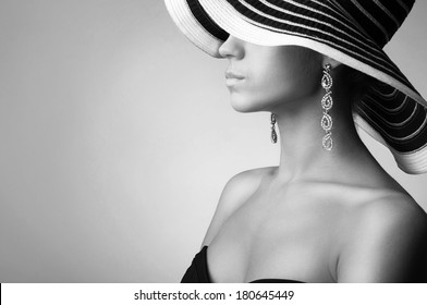 Black and white photo of young sexy woman in hat and long earrings