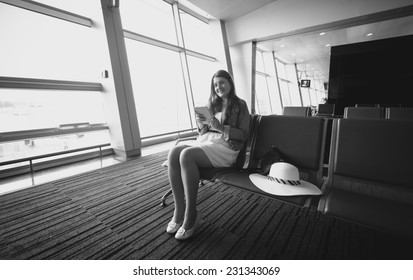 Black and white photo of young woman sitting in airport terminal and using tablet