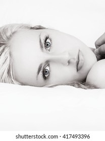 Black and white photograph of beautiful blond haired blue eyed young woman laying on white sheets and looking into the camera