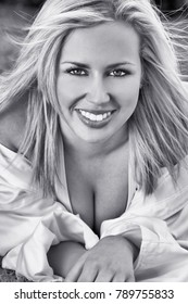 Black and white photograph of beautiful blond haired model with perfect teeth, wearing a white shirt shot outside using natural light