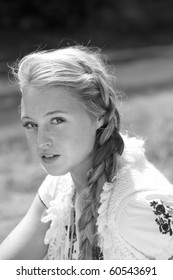 A black and white photograph of a beautiful blonde girl in country clothing and braids