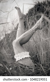 Black and white photograph of a bridal garter on beautiful and slim female legs