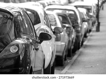 Black and white photograph of cars parked in city centre