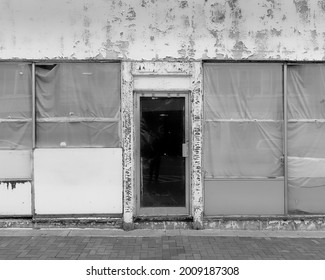 Black and white photograph of a closed storefront. Plastic on windows, peeling paint, blistering stucco. Entry is dead center.