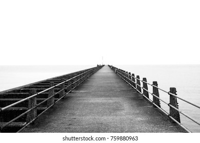 black and white photograph of a concrete straight jetty with converging metal railings jutting out into the sea in the distant to a horizon and vanishing point a flat calm sea on either side
