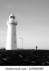 Black and white photograph of Donaghadee Lighthouse and silhouette of fisherman. Northern Ireland