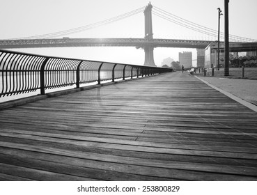 A black and white photograph of the Manhattan Bridge, taken from a wooden walking path in Brooklyn Bridge Park.