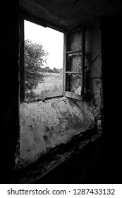black and white photograph of open smashed window in an old derelict disused flour mill, Langwith, Mansfield, Nottinghamshire, England, UK