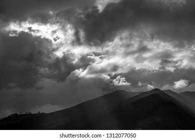 Black and white photograph of the Pichincha volcano seen from Quito city at sunset with a wonderful sunbeam, Andes mountain range, Ecuador.