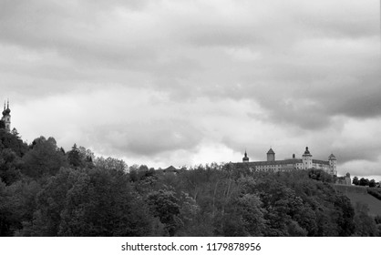 A black and white photograph of Salzburg Castle. Forest covers the slope of a hill in the foreground. The sky is cloudy.