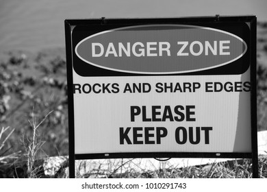 black and white photograph sign danger zone rocks and sharp edges please keep out by water florida